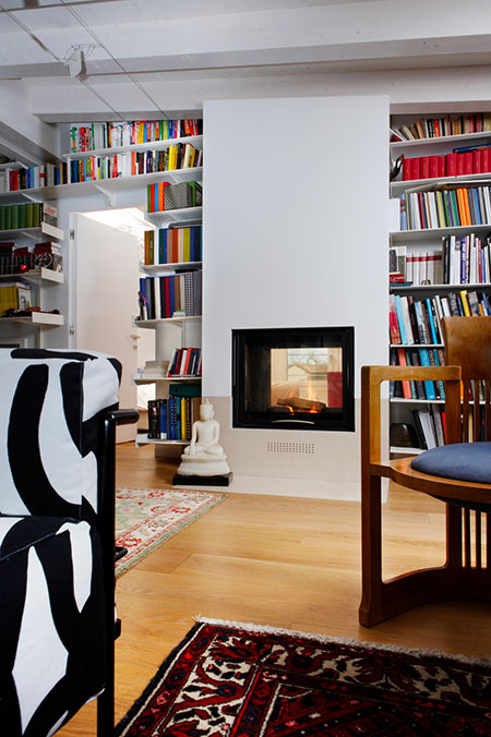 Wood fireplace in a bookcase by MCZ